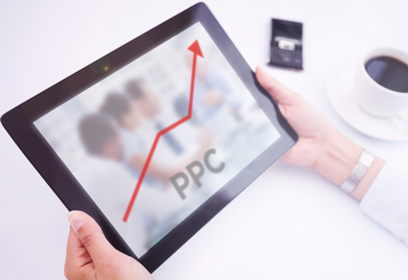 an image of tablet screen showing a line graph starting from the bottom and going up (in Red) showing the performance of an Adwords campaign against a blurred out image of four consultants sat around a table with the words PPC positioned middle bottom