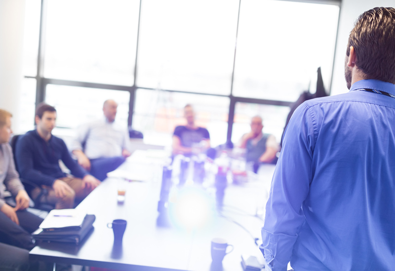 an image showing a public relations consultant standing up and giving a presentation talk to a number of employees sitting around a table